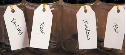 Photo of jars with money in the jar earmarked for certain categories such as parking, roof, windows and pool