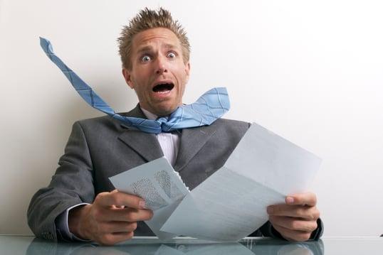 Photo of a man looking at a bill
