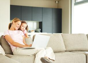 Photo of a mother and her daughter looking at a laptop