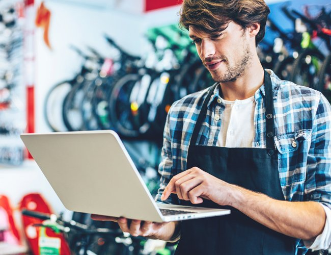 bicycle shop owner on laptop