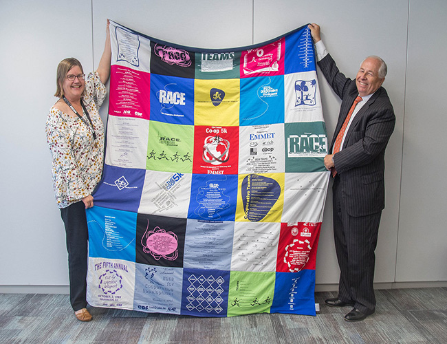 Man and Women holding a Cooperative Development Foundation quilt