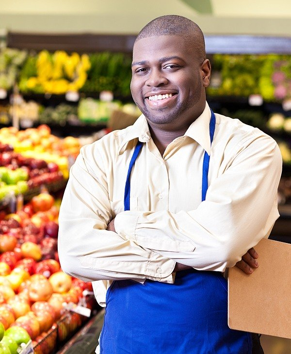 business owner standing in his grocery store