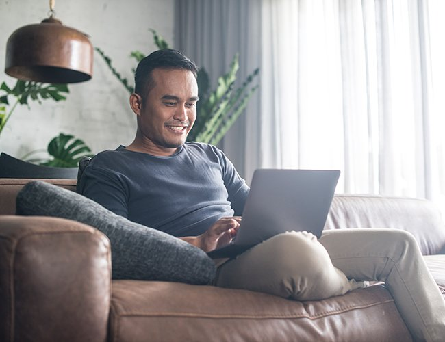 man sitting on couch smiling at laptop