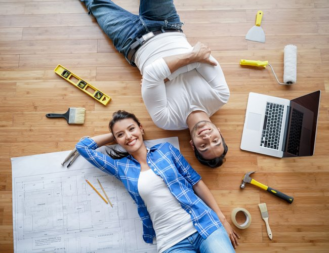 couple laying on the floor with remodeling items scattered around