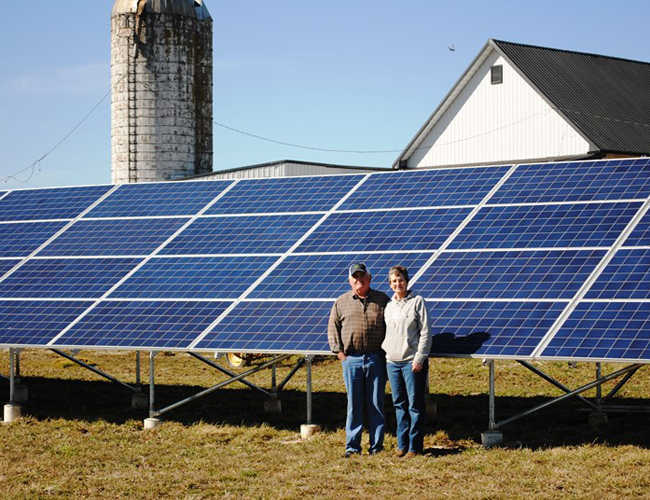 NCB customers standing in front of their solar panels