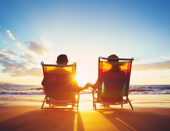 retired couple watching sunset on beach